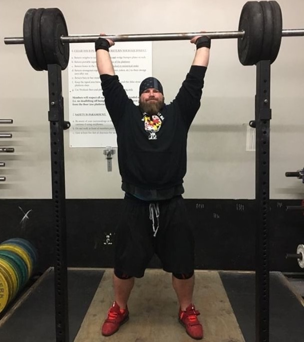 Jon Ward from Colosseum Strongman Performing A Front Barbell Press off the Rack