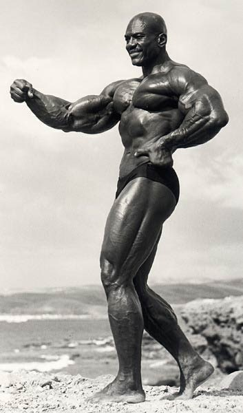 Sergio Oliva flexes his massively muscular arms.