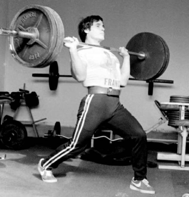 Franco Columbu power cleaning a 315 lb barbell using the shallowest of splits