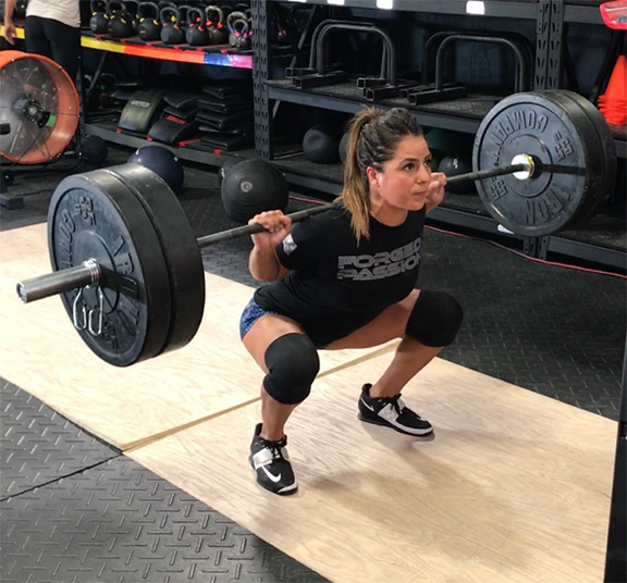 IRON COMPANY and Crossfit athlete Jackie Perez back barbell squatting with rubber bumper plates, Olympic weightlifting bar on top of a weightlifting platform.