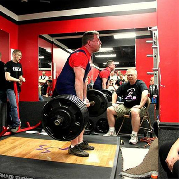 IRON COMPANY athlete Marty Gallagher performing a barbell deadlift on a weightlifting platform.